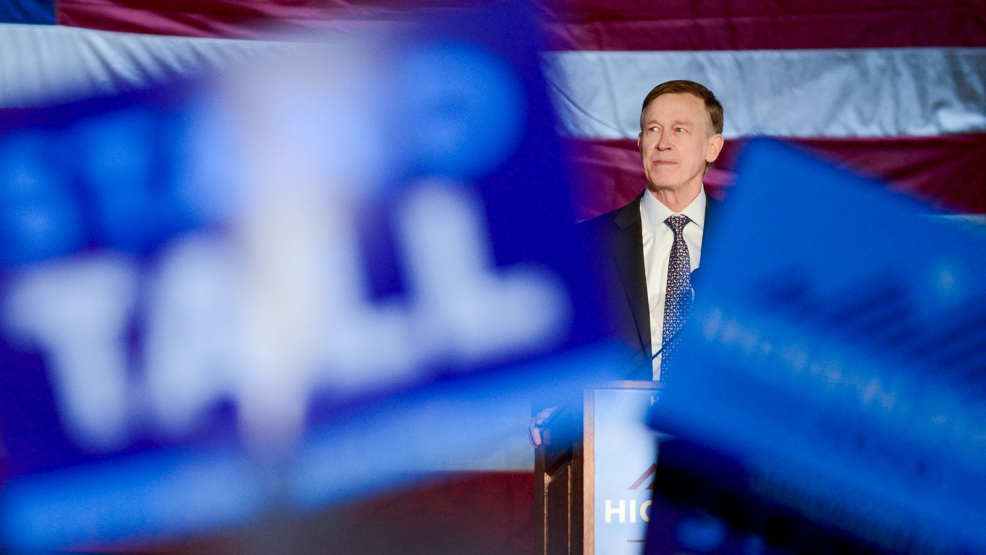 Hickenlooper speaks from behind a podium at a campaign rally, framed by blue signs.