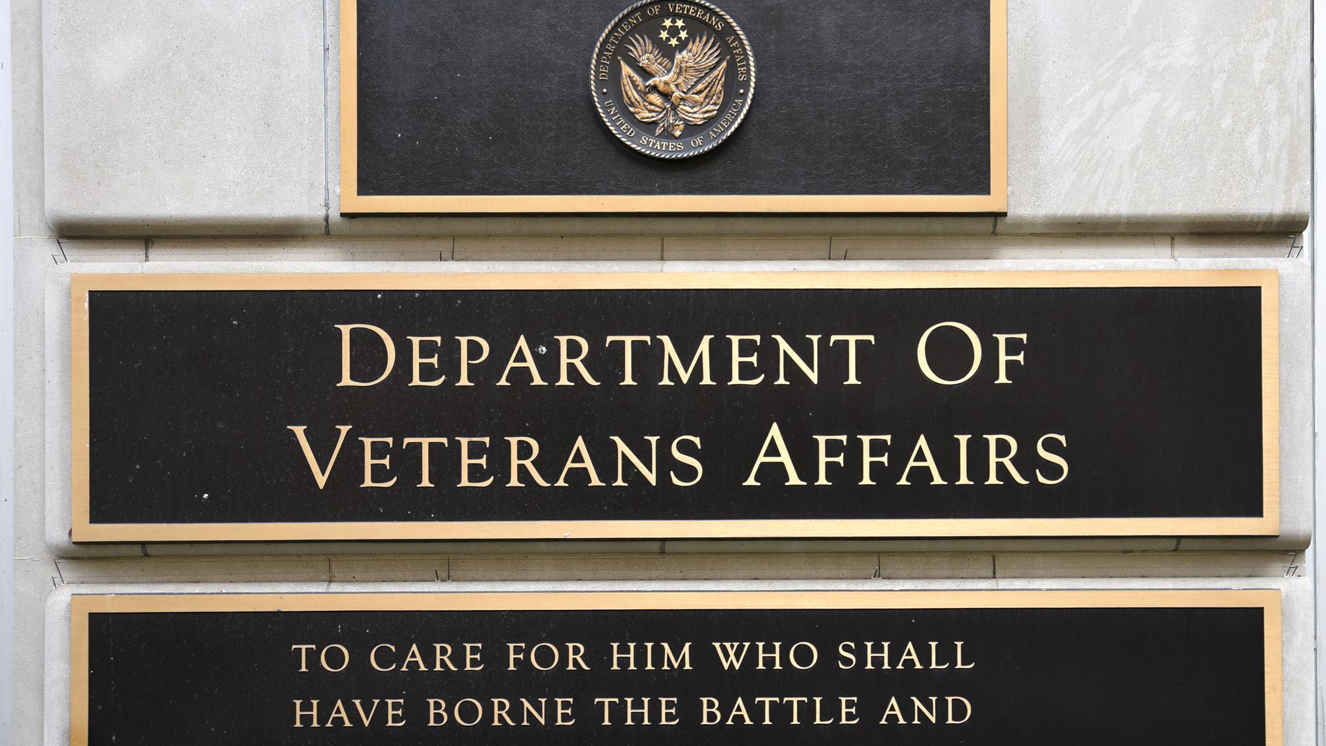 "A plaque outside the VA that reads, ""To care for whim who shall have borne the battle..."""