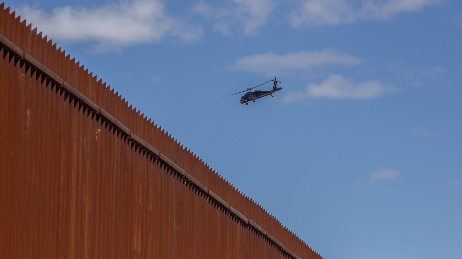 In this image, a helicopter flies over a border wall.