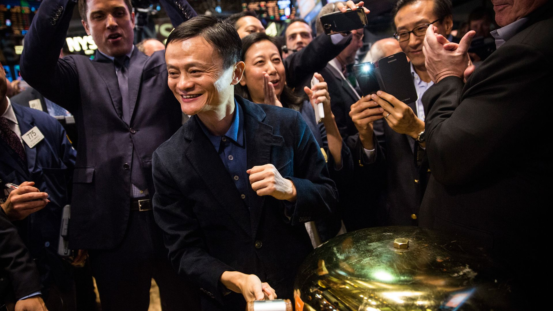 Jack Ma rings a bell, surrounded by cheering people
