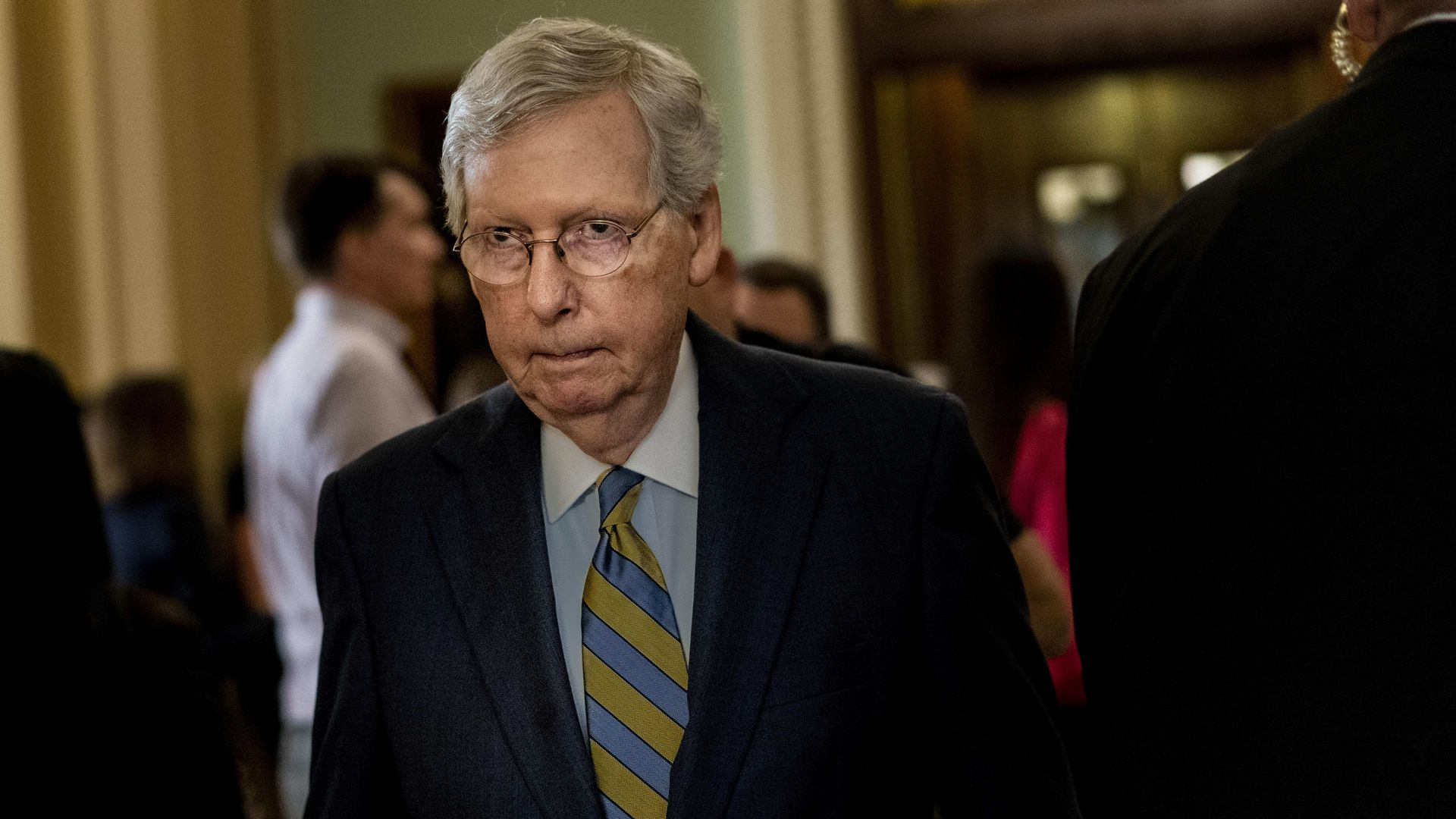 In this image, McConnell wears a stripe tie and a suit and walks through a crowded hallway.