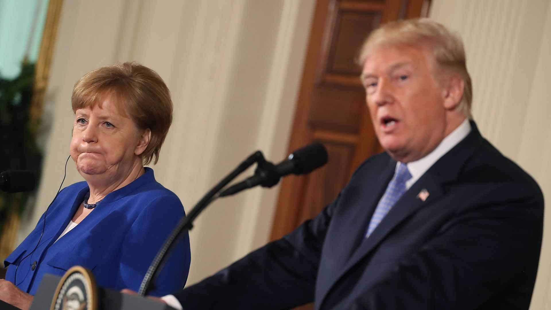 Angela Merkel puffs out her cheeks looking sideways at Trump.