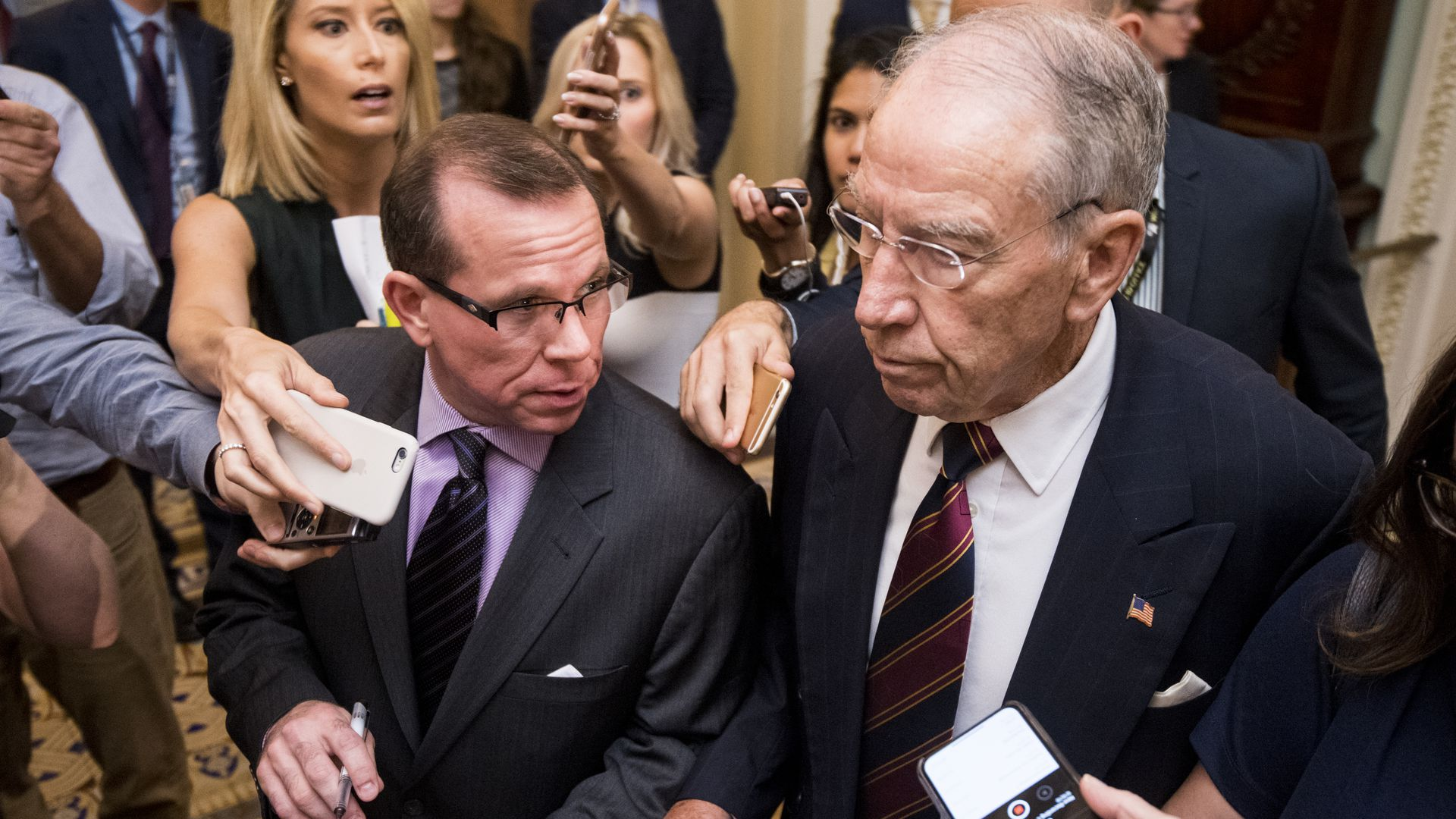 Senator Chuck Grassley surrounded by reporters asking questions.