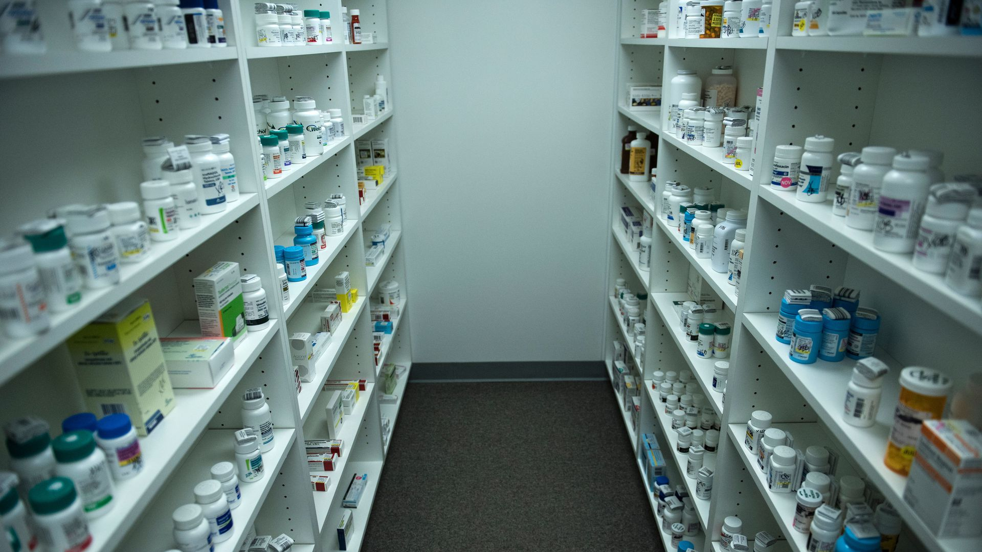 Shelves in a pharmacy are stocked with prescription drugs.
