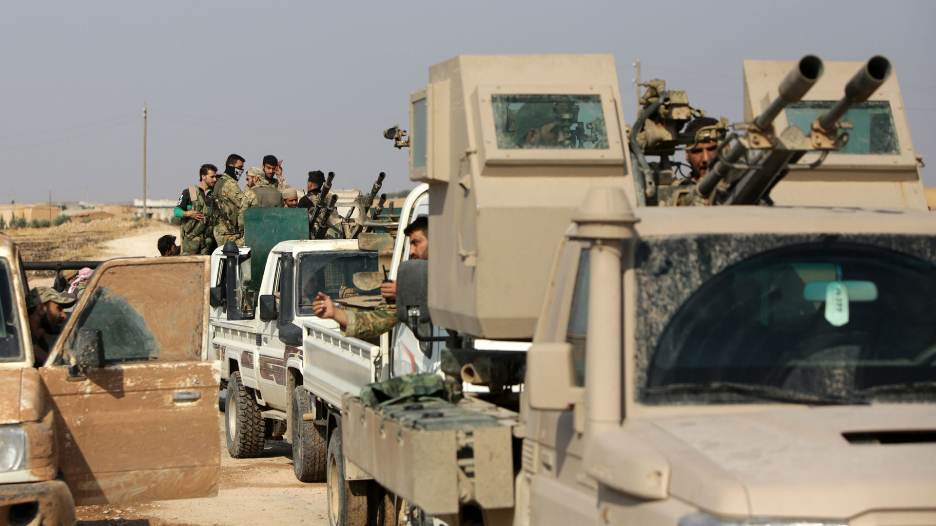 Turkey-backed Syrian fighters gather on a road between the northern Syrian towns of Tal Abyad and Kobane on October 22