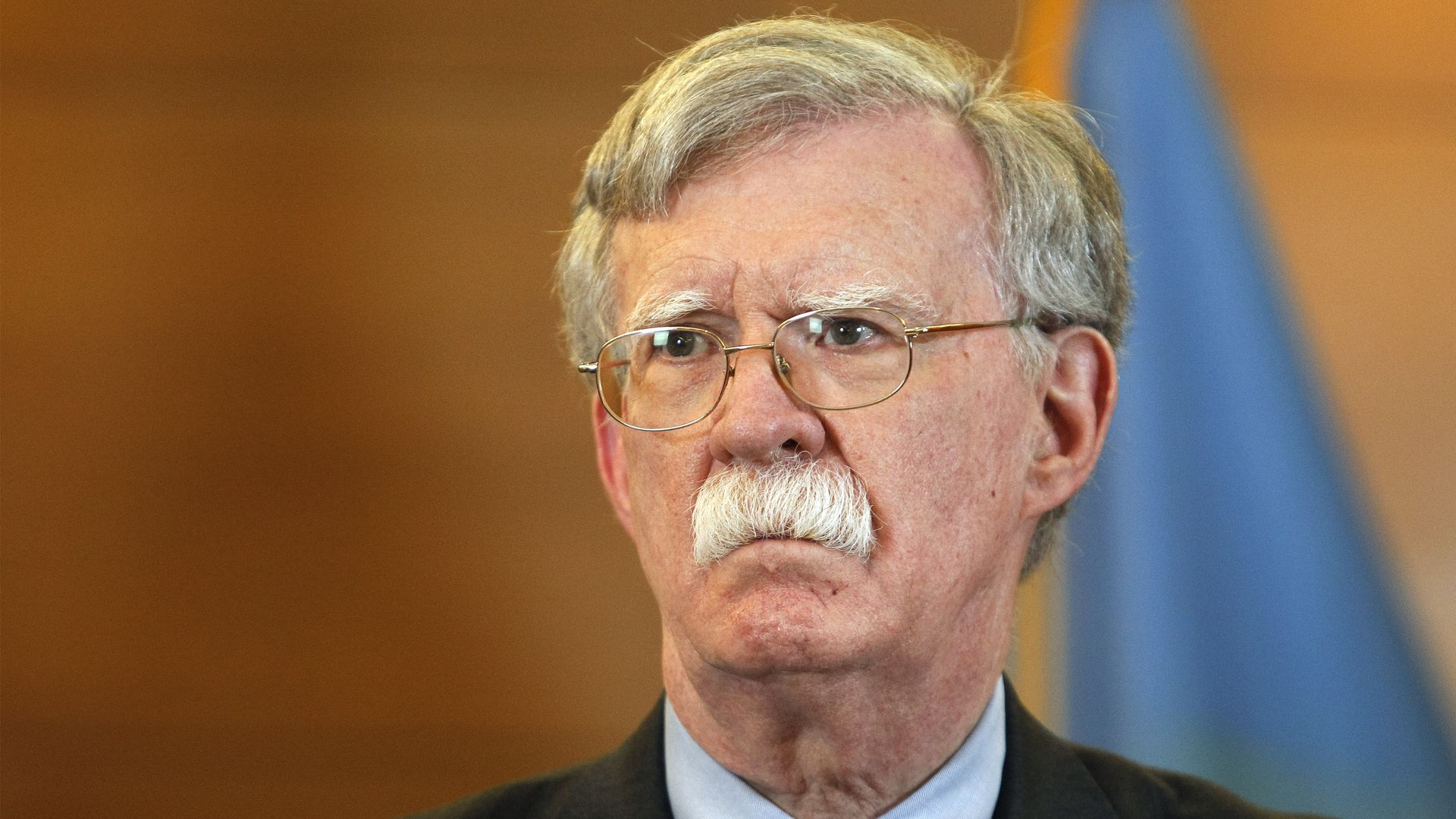 John Bolton in front of a Ukrainian flag