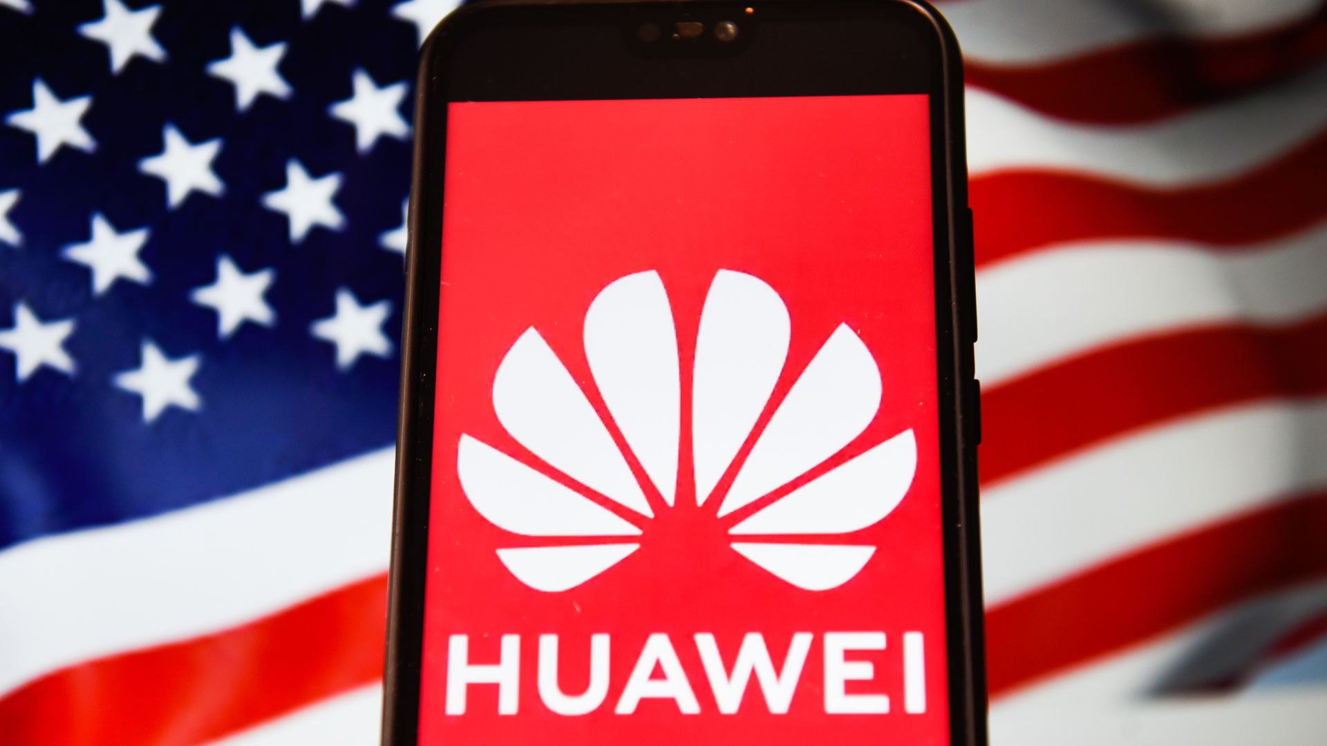 This photo shows the Huawei logo displayed on a phone with the American flag in the background.