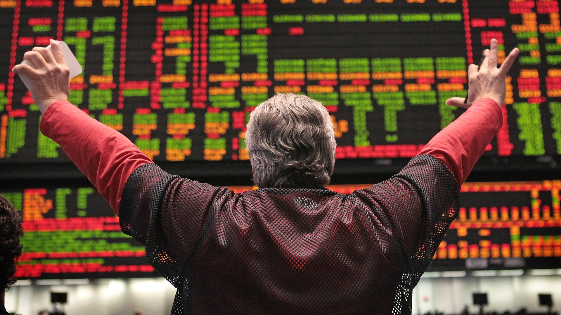 Man with back toward camera with arms in cheering position looking at the stock market ticker