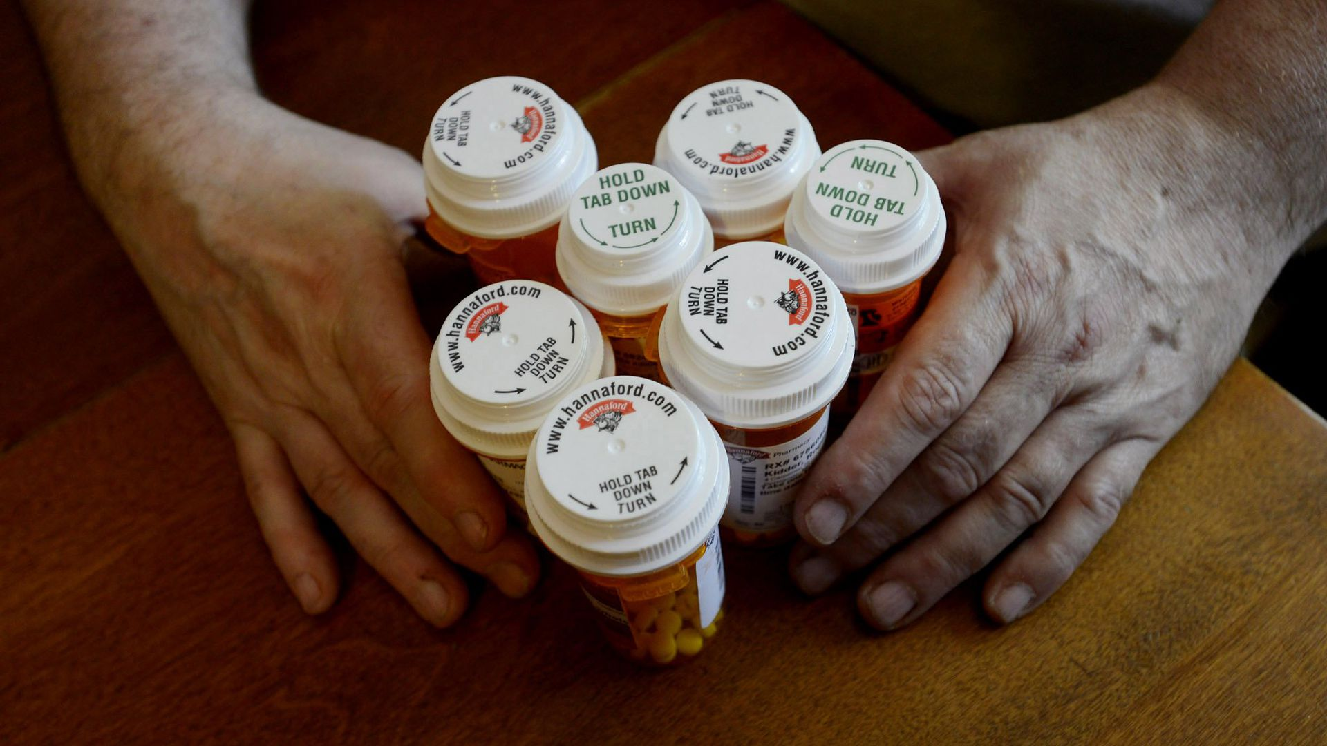 A person holds seven bottles of prescription drugs.