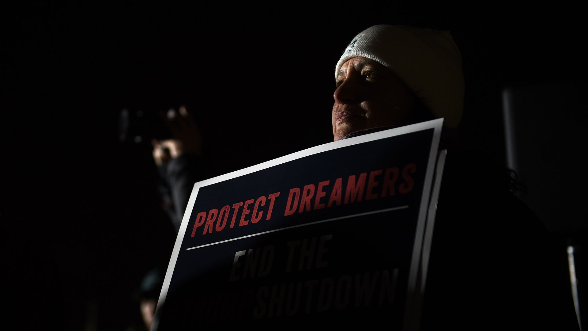 "Woman carrying a ""protect dreamers"" sign. Dark photo"