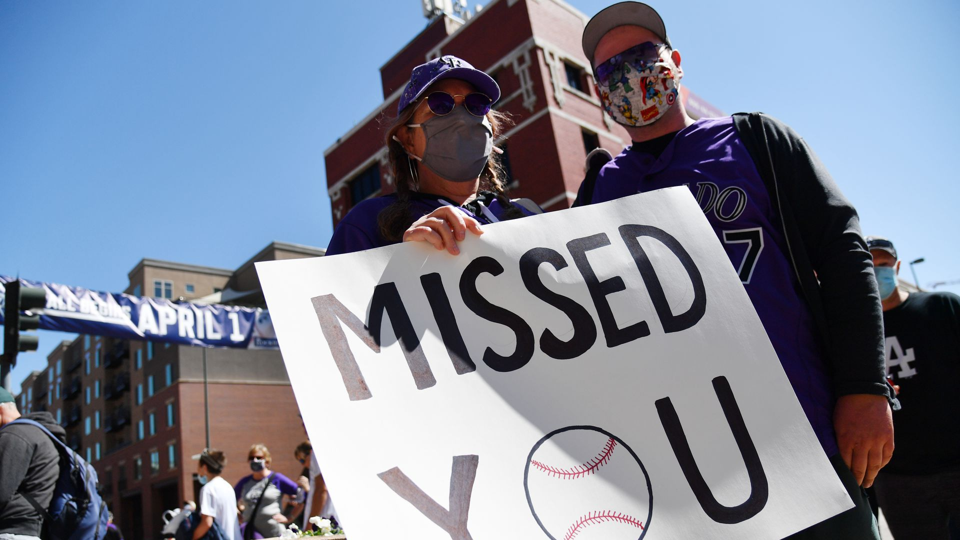 Two baseball fans hold a sign that reads Missed You