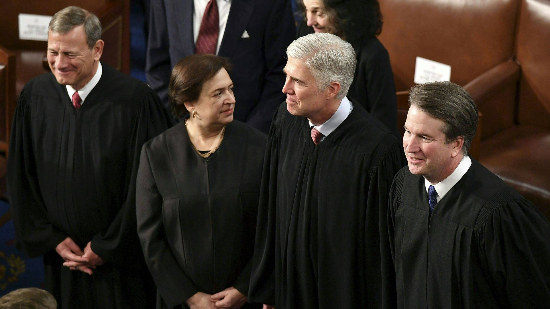 In this image, the Supreme Court justices stand in a line