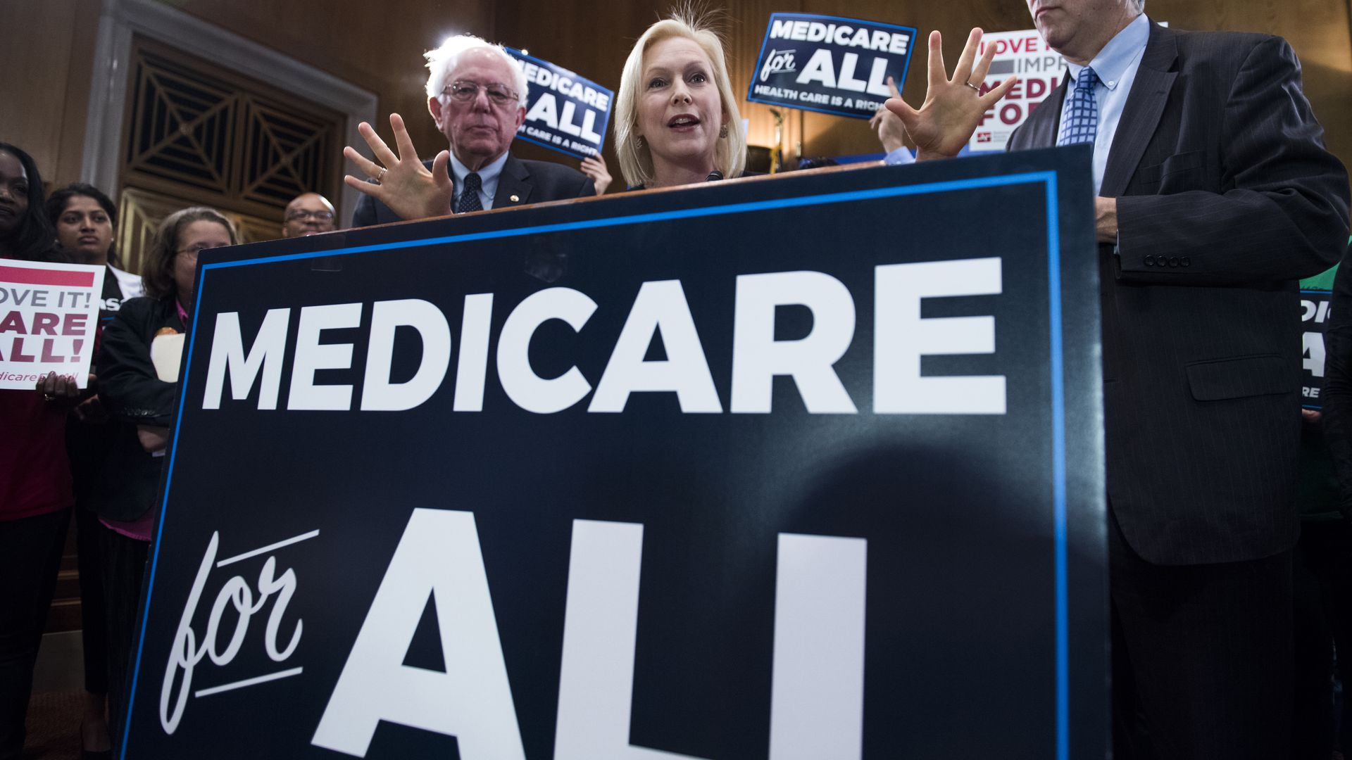 Kirsten Gillibrand ans Bernie Sanders standing behind a medicare for all sign