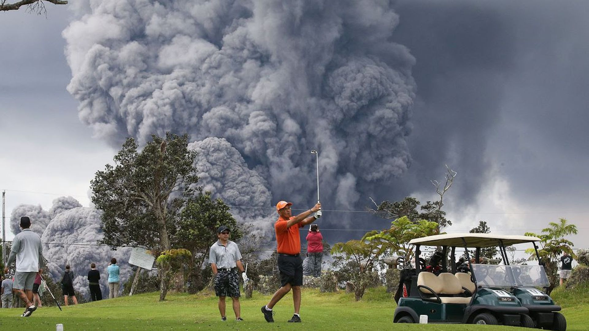 The Kilauea Volcano eruption looms behind a golfer in Hawaii Volcanoes National Park on May 15, 2018.