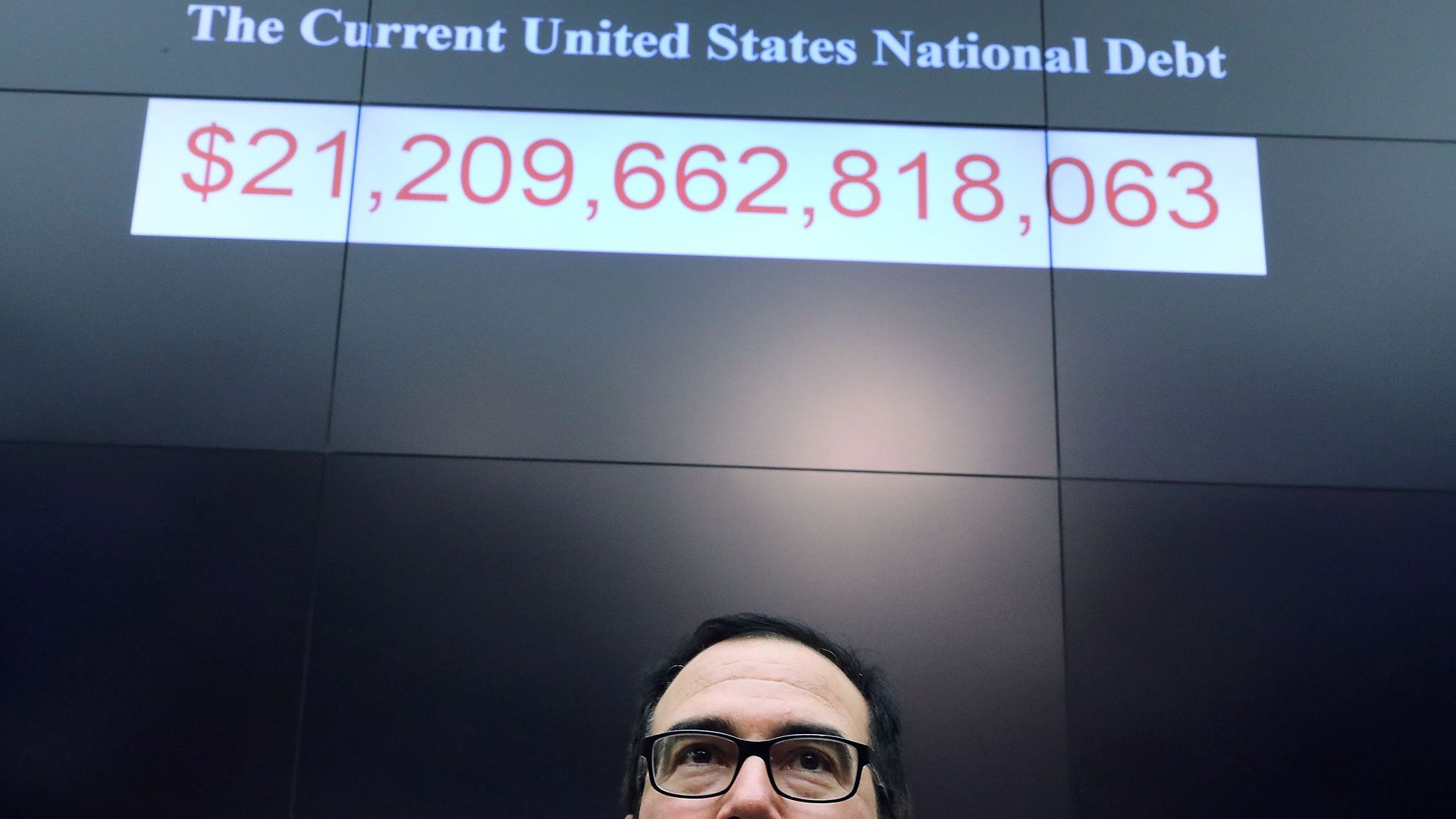 Steven Mnuchin standing under a sign that details the U.S. National Debt.