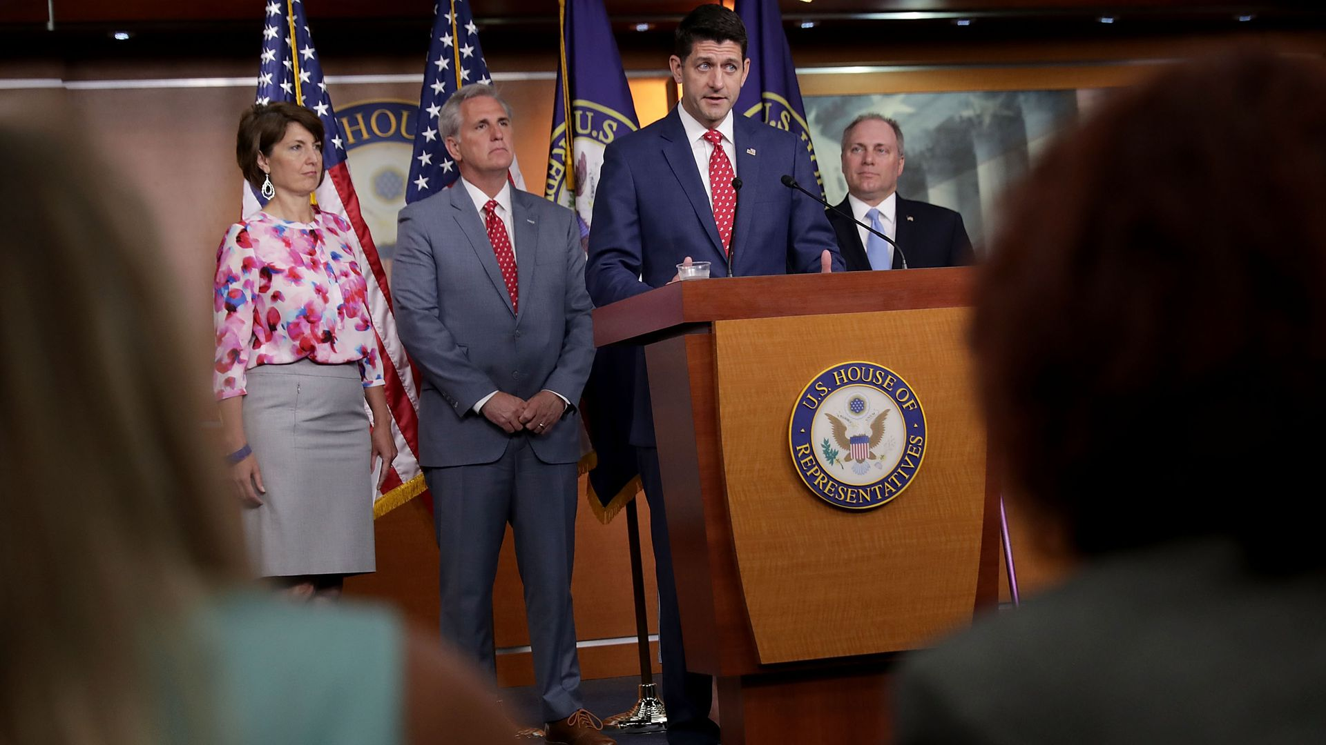 Paul Ryan answering questions at a podium with other GOP House leaders