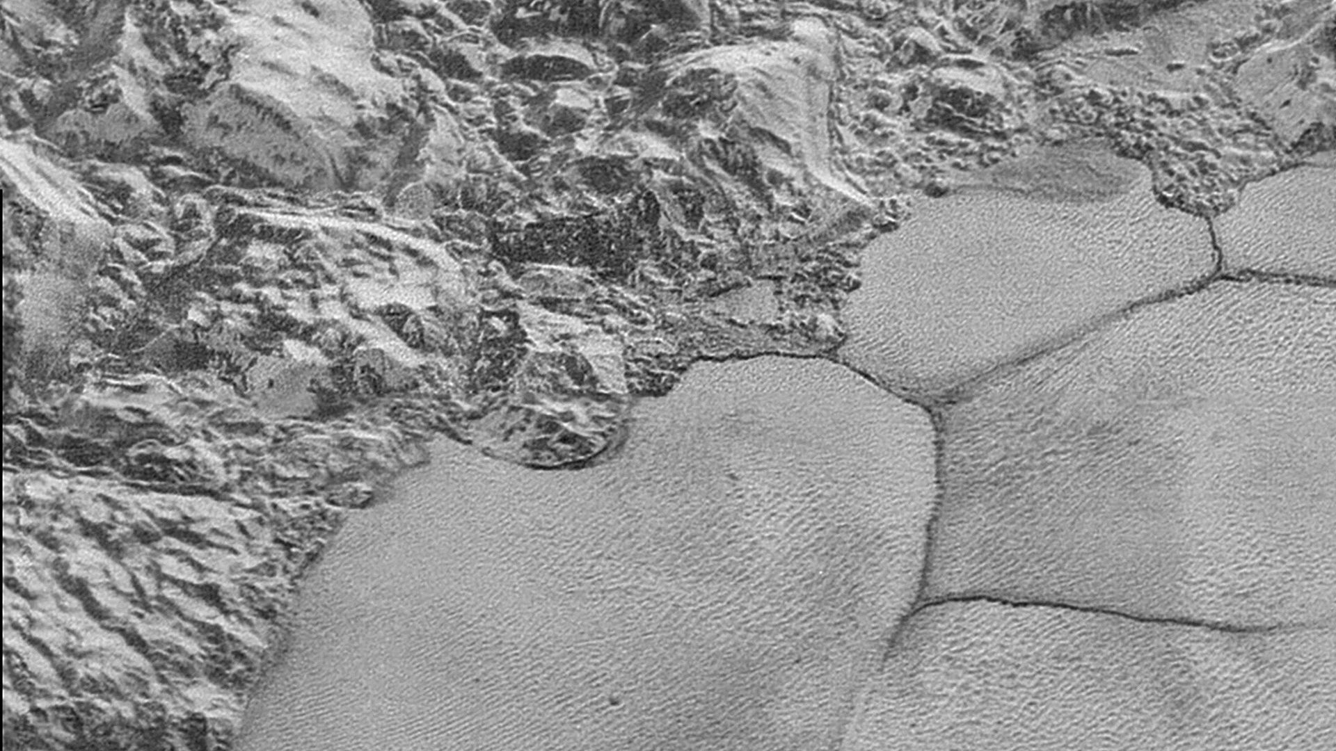 The mountain range on the edge of the Sputnik Planitia ice plain, with dune formations in the bottom half of the picture.