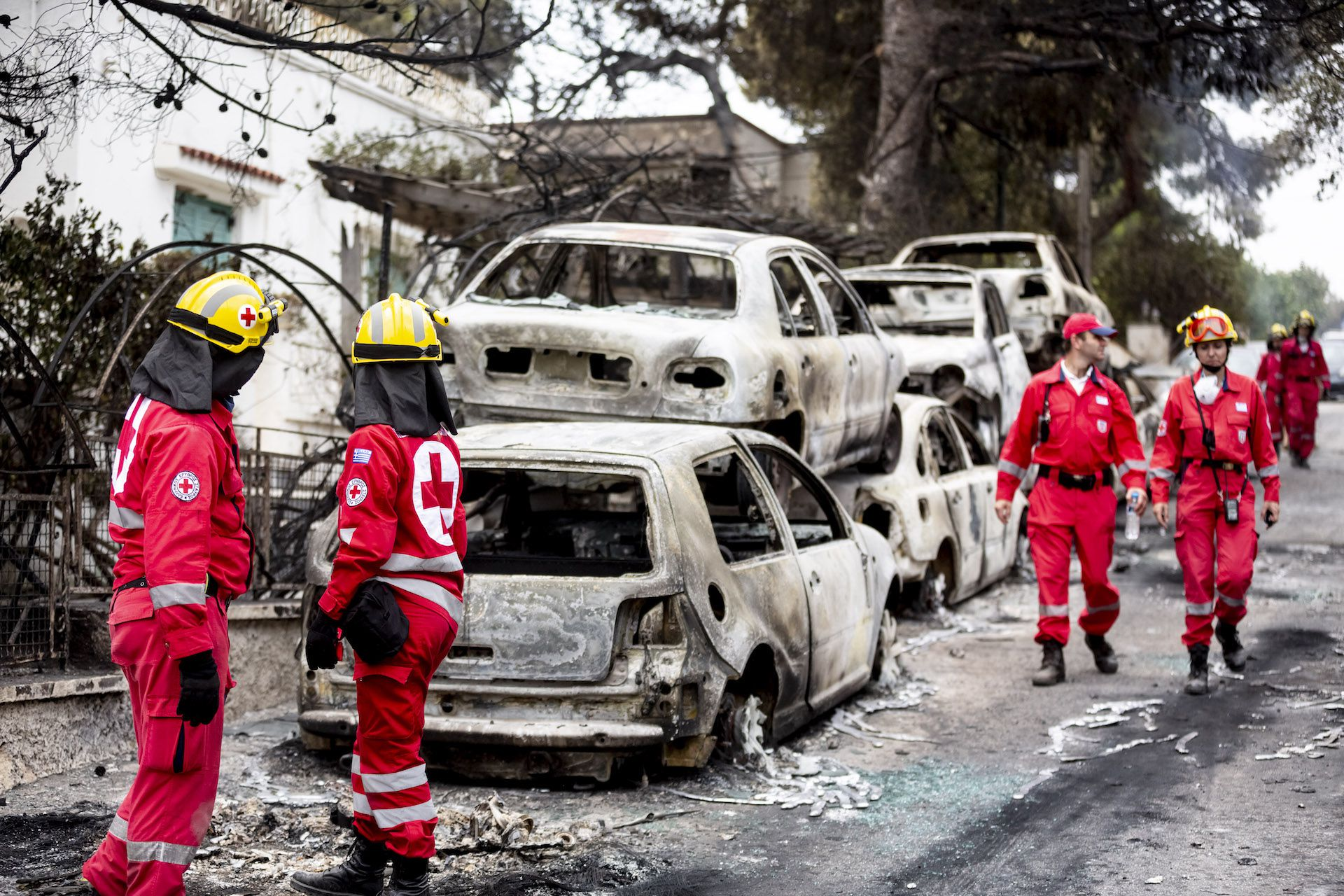 Forces of the Greek Red Cross stand on a road next to burnt cars after a fire raged in Mati, Greece on July 24, 2018.