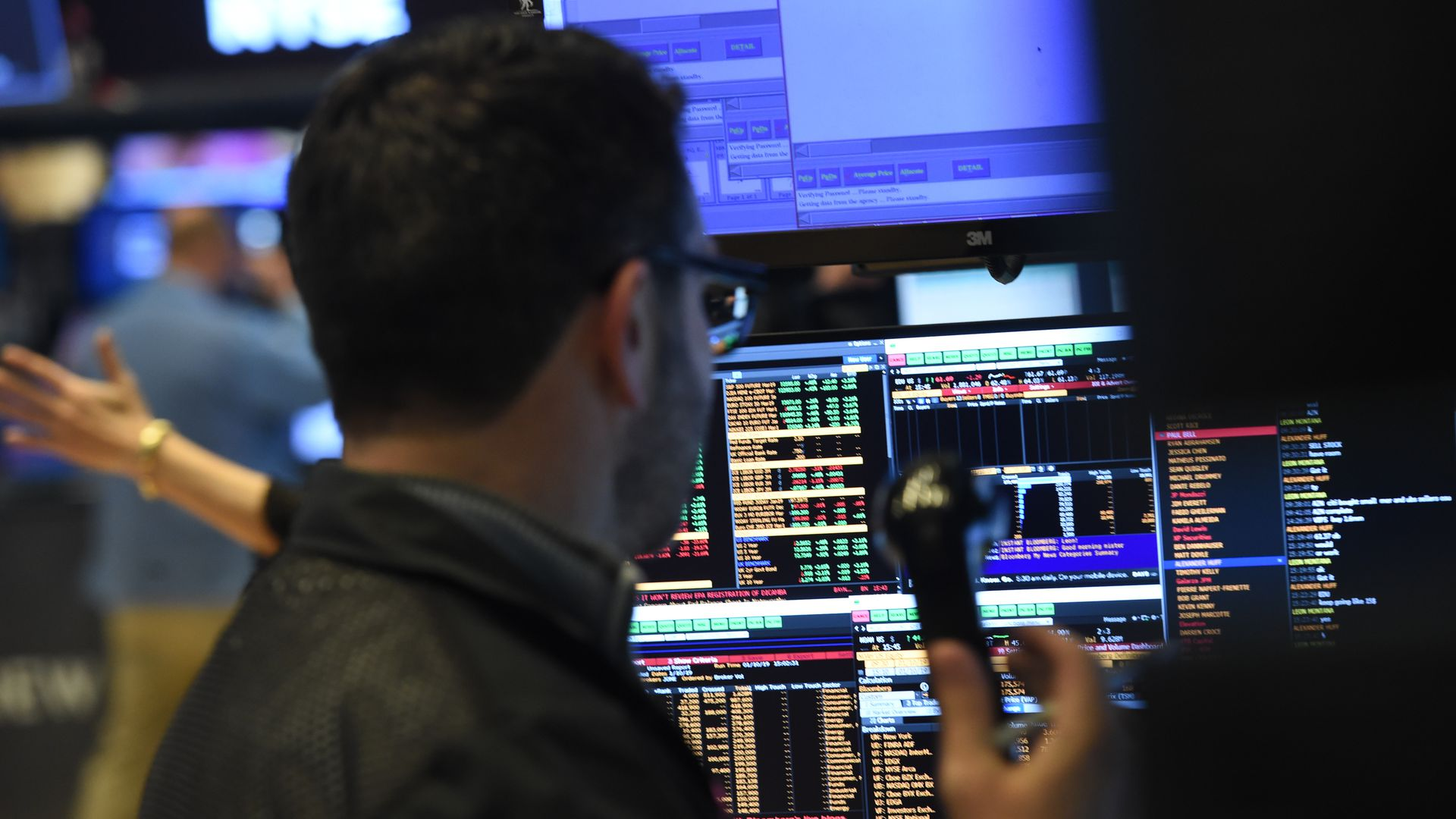 In this image, a broker at the New York Stock Exchange stands with a telephone in front of screens.
