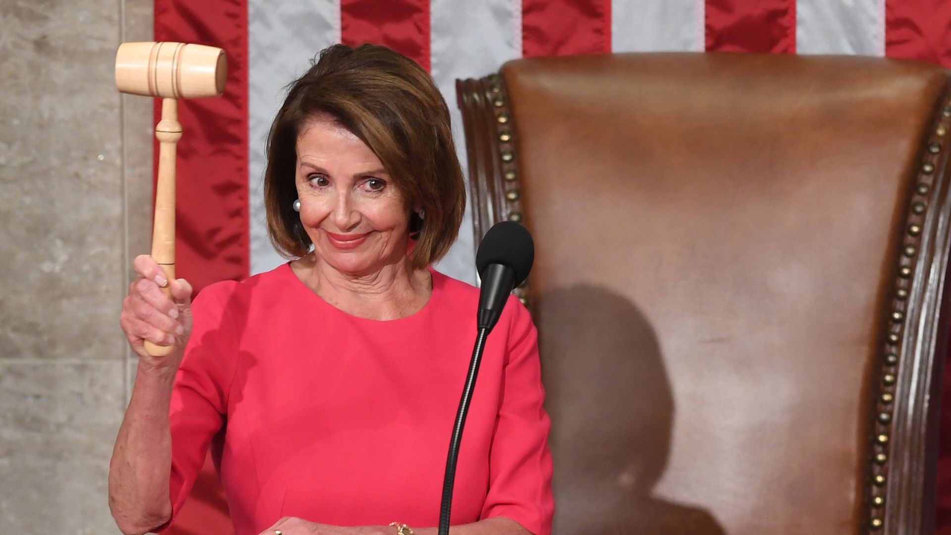 In this image, Pelosi holds a gavel up.