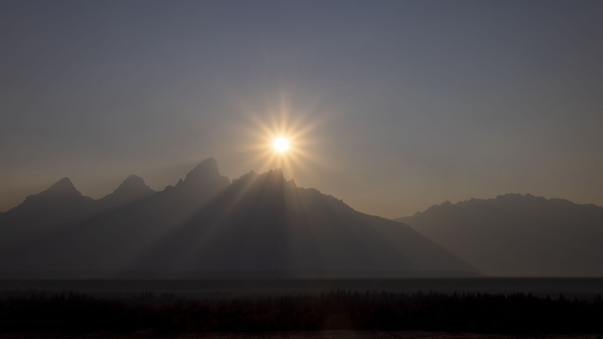 The sun sets behind the Grand Teton peak, shrouded in smoke from regional wildfires July 14, 2021 at Grand Teton National Park.
