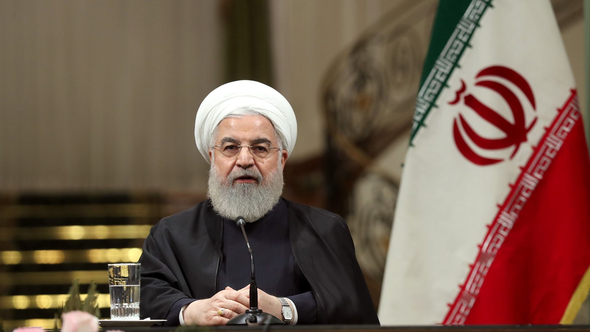 Hassan Rouhani seated at a press conference