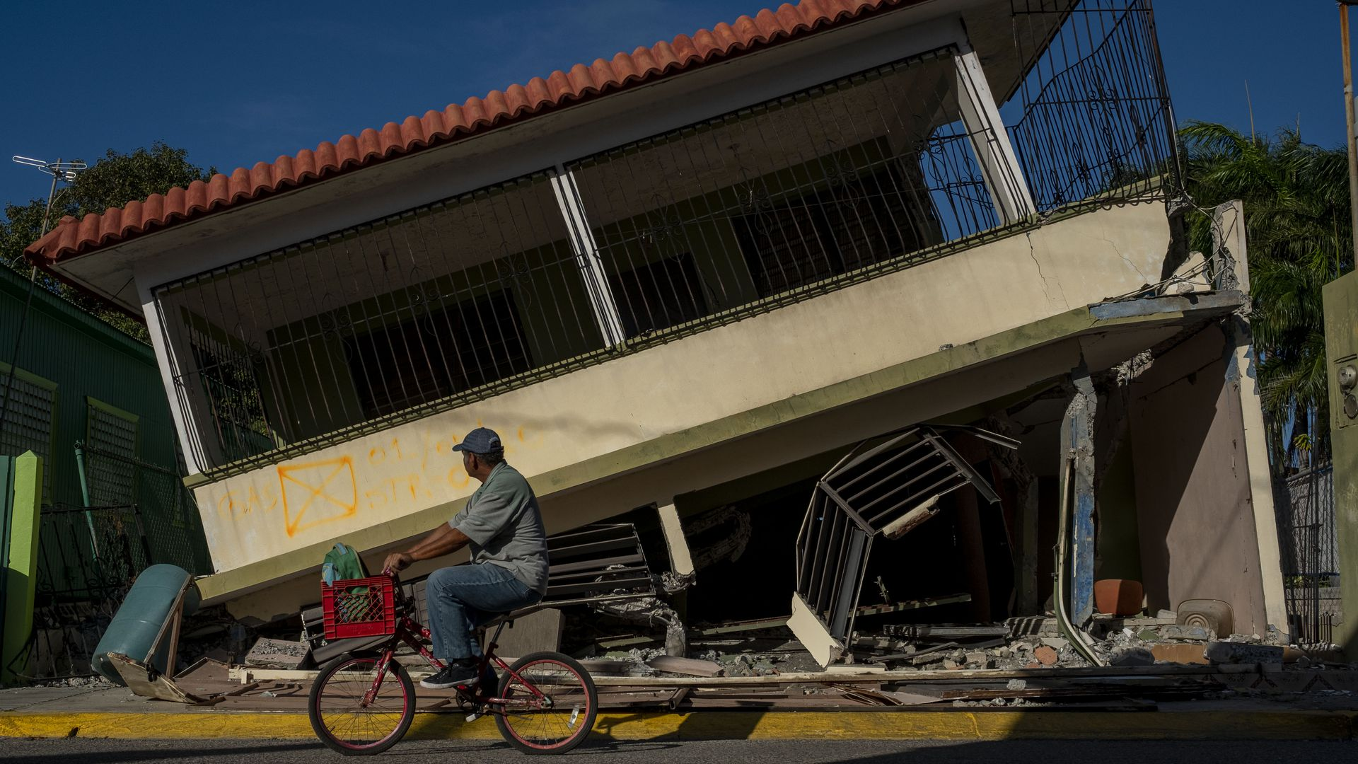 In this image, a Puerto Rican man bikes past a lopsided building.