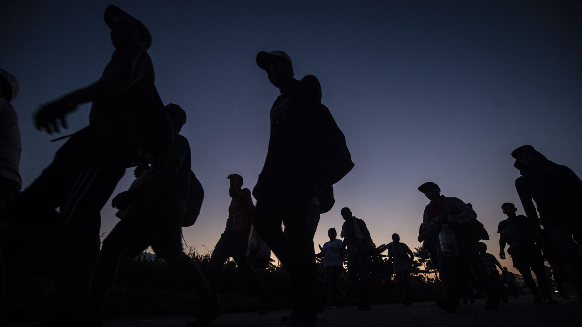 Silhouettes of people marching in a caravan before a pink and blue dark sky.