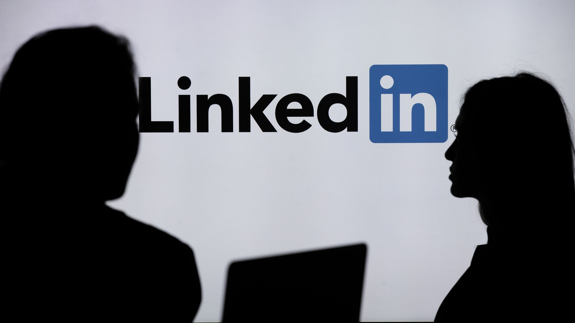 People in a shadow with the LinkedIn logo in the background.