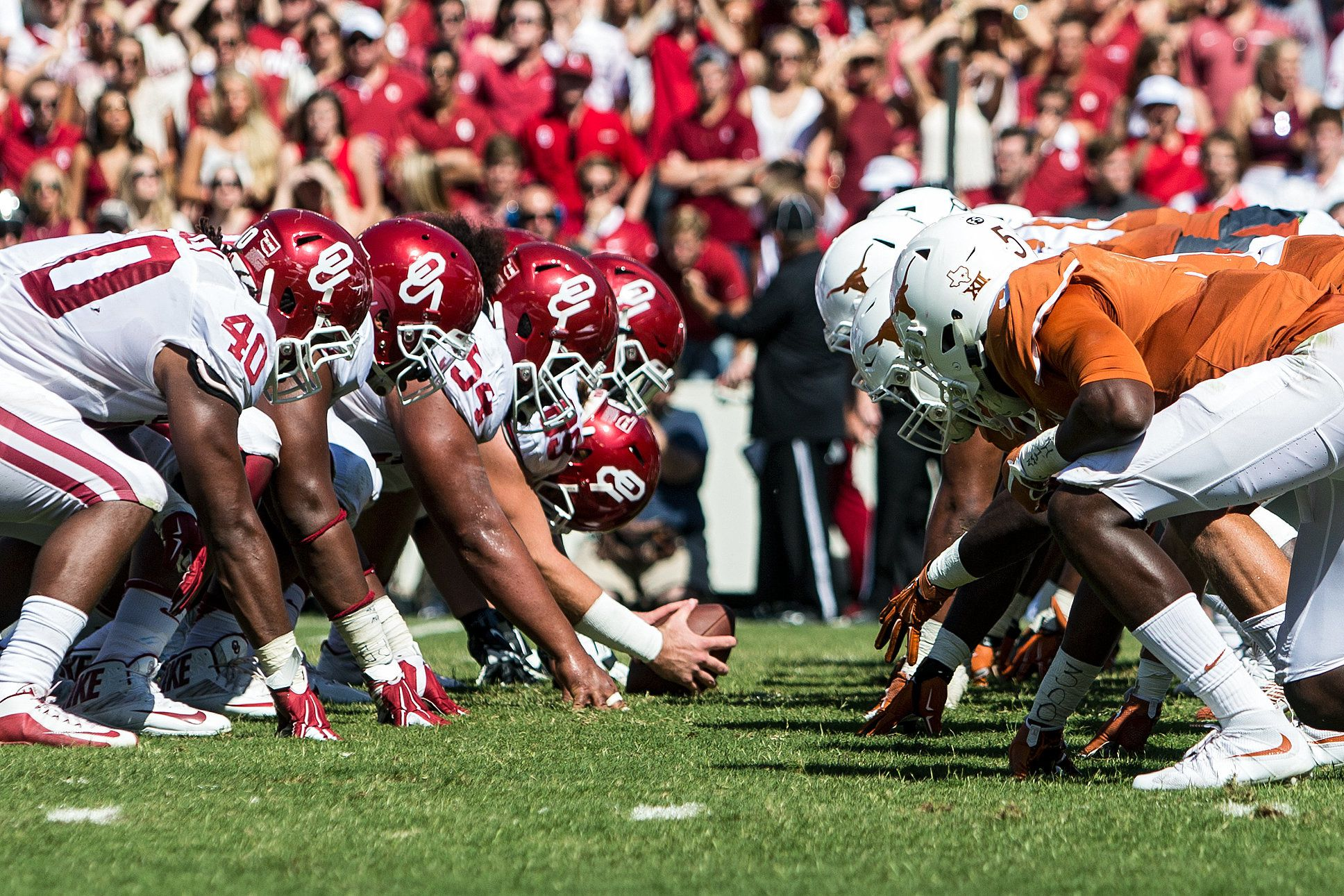 Players from both Oklahoma and Texas line up on either side of the football.