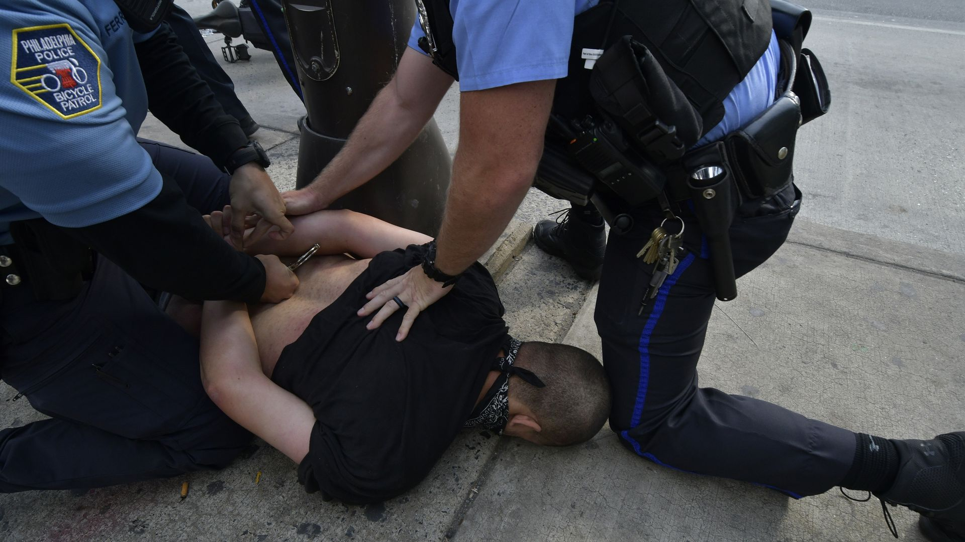 Police officers arresting someone after a police brutality protest