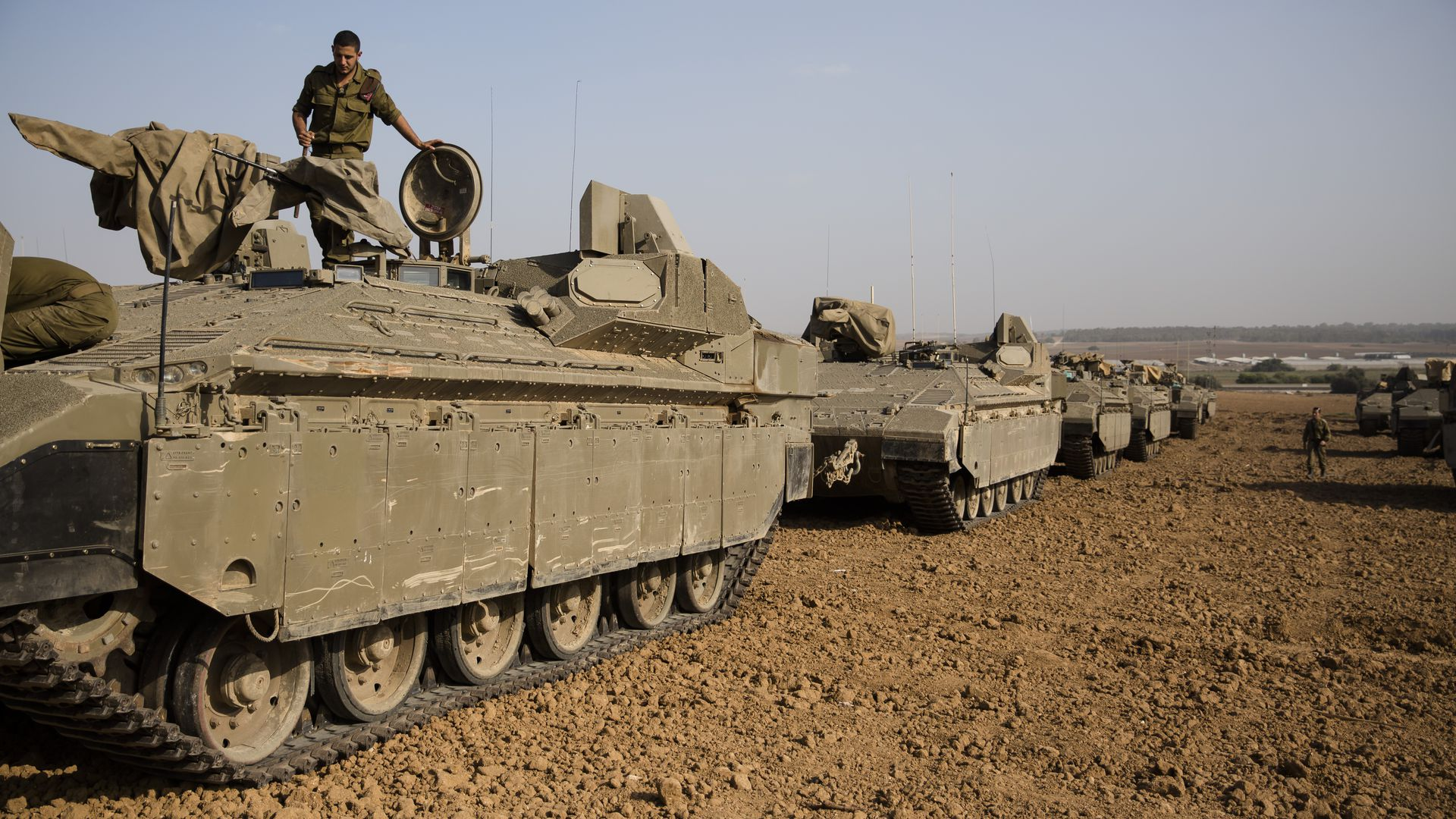 An  Israeli soldier stands on top an armoured personnel carrier near the border with Gaza