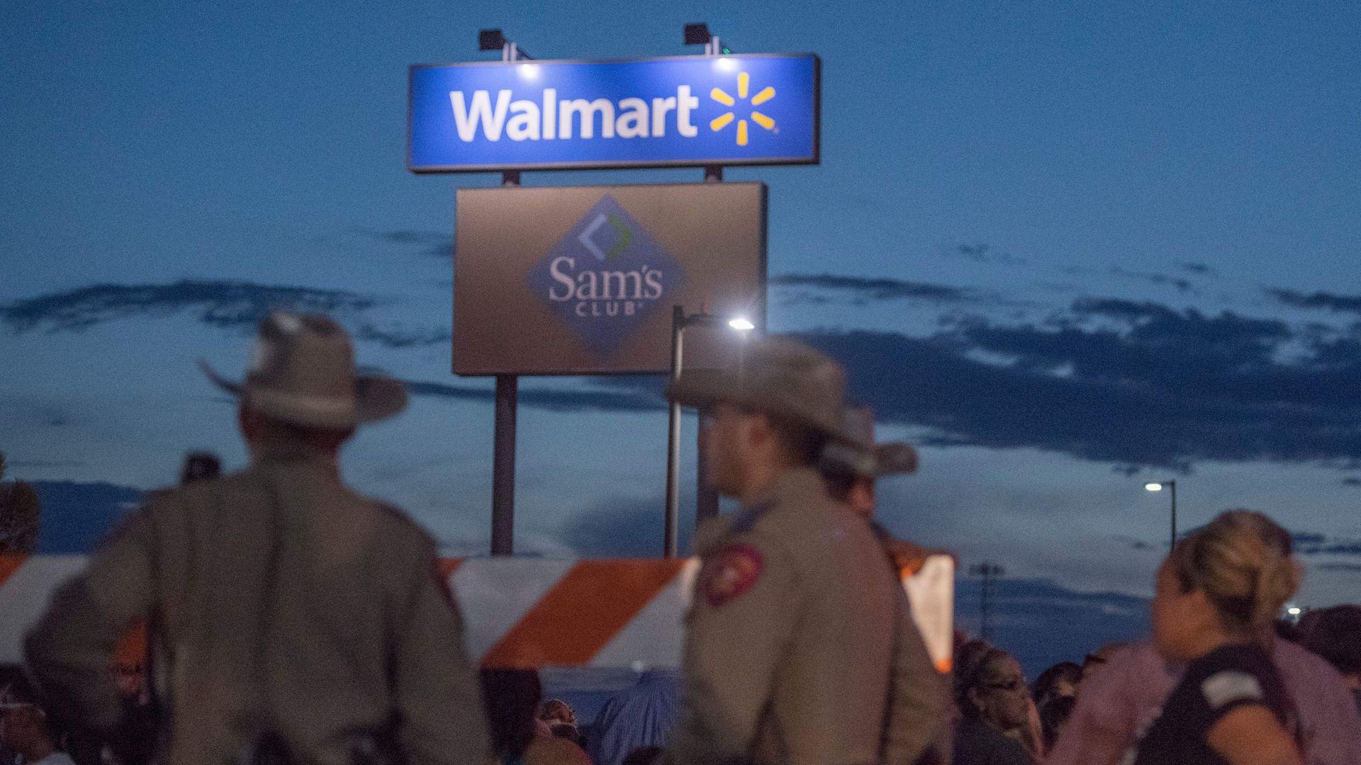 In this image, law enforcement stand in a Walmart parking lot at night. The Walmart logo is on a tall sign behind them.