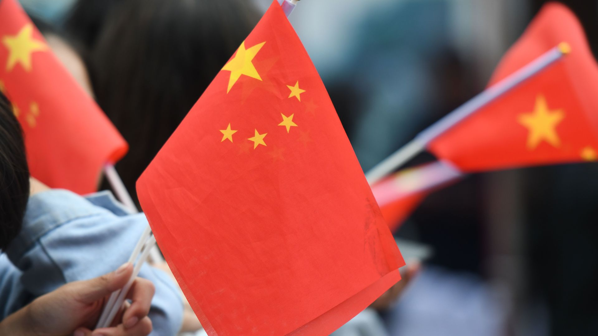 People wave miniature Chinese flags.