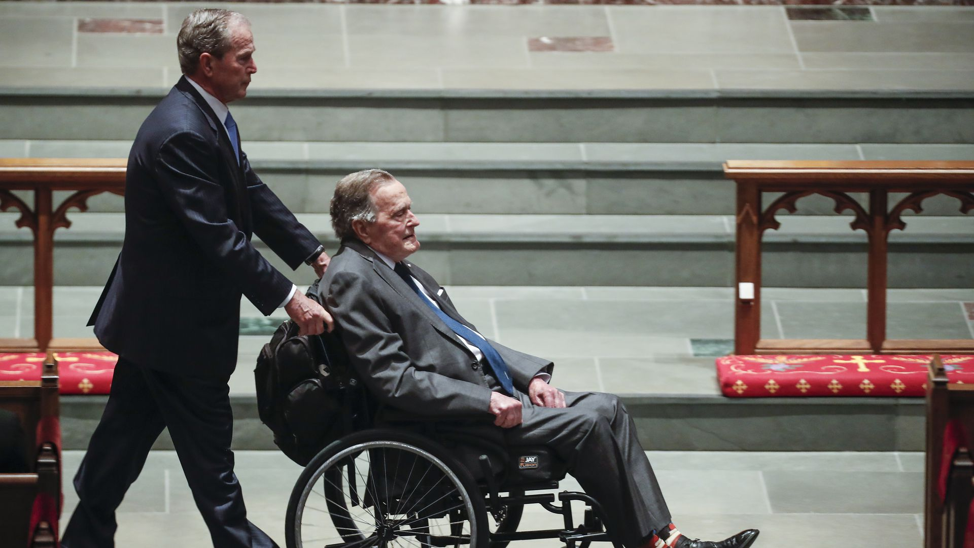 Former president George W. Bush pushes his father, George H.W. Bush, in a wheelchair at Barbara Bush's funeral