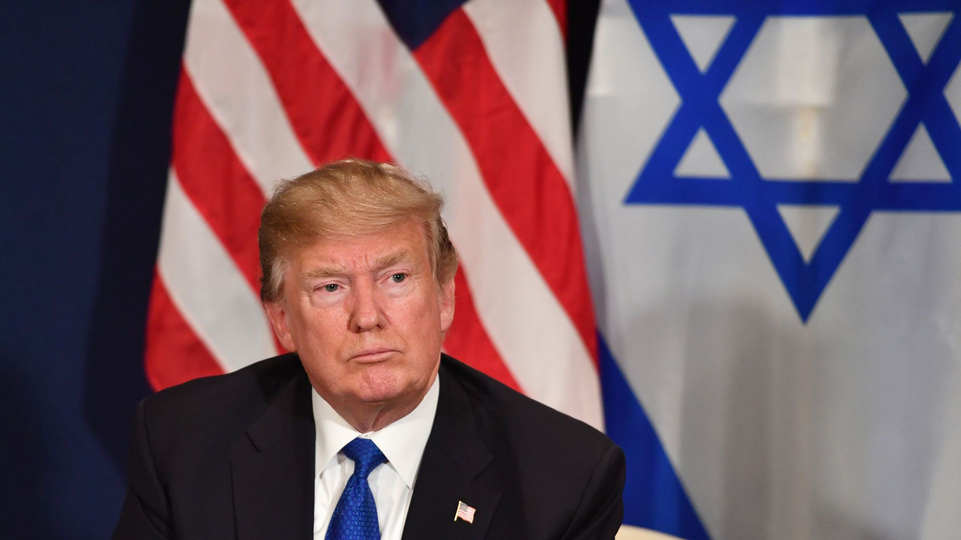Trump with USA and Israel flags behind him