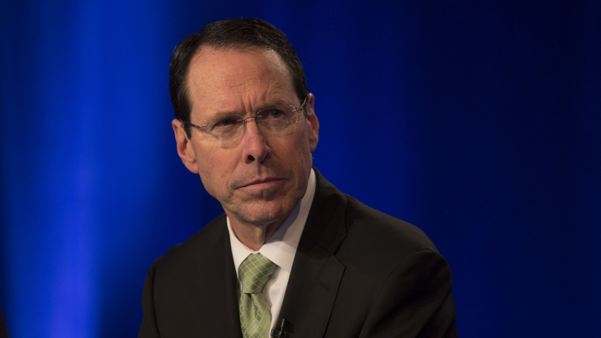 AT&T CEO Randall Stephenson sits in front of a blue backdrop