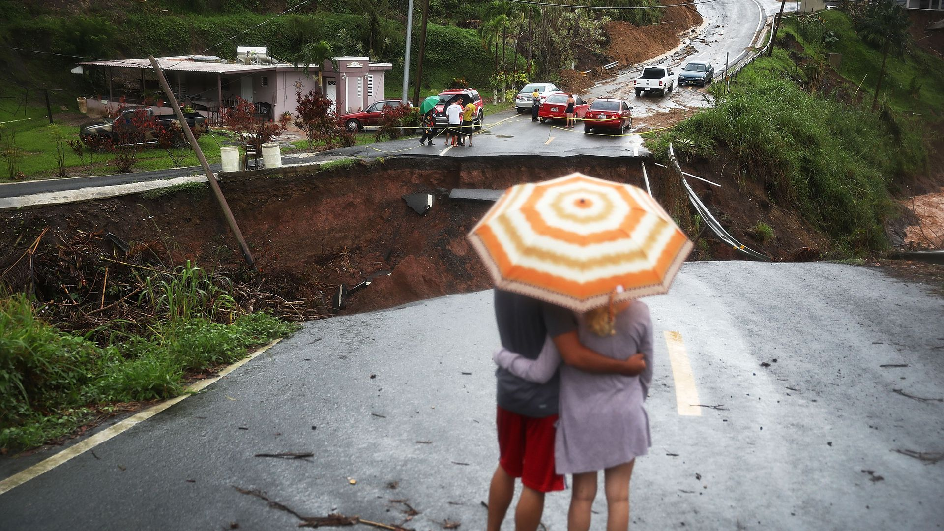 People look on at a section of a road that collapsed in Barranquitas, Puerto Rico after Hurricane Maria swept through the island in 2017.