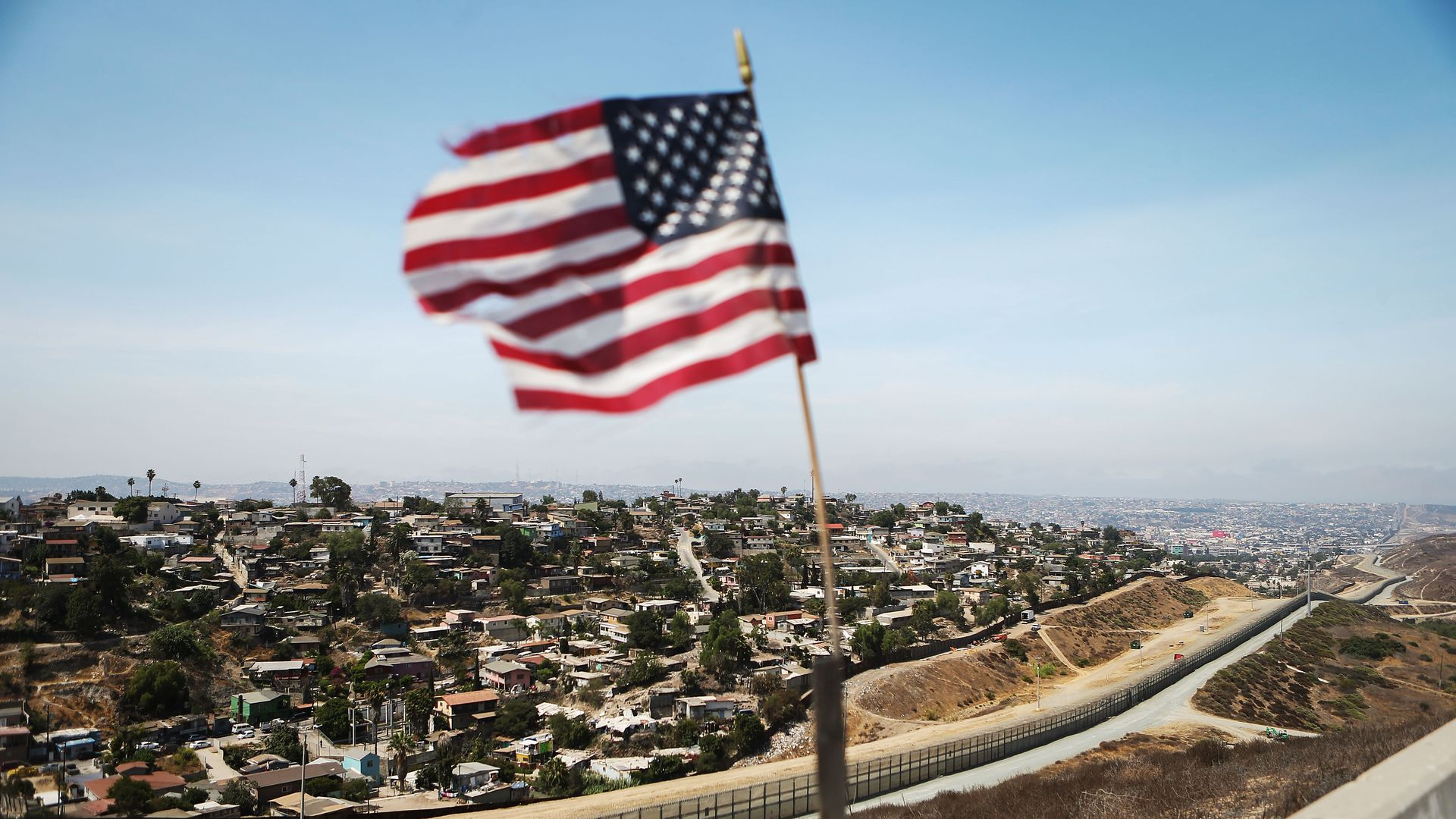 American flag flying above border with Mexico