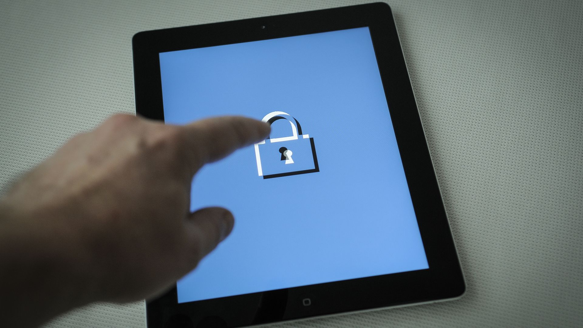 Finger pointing at a lock illustration on a tablet