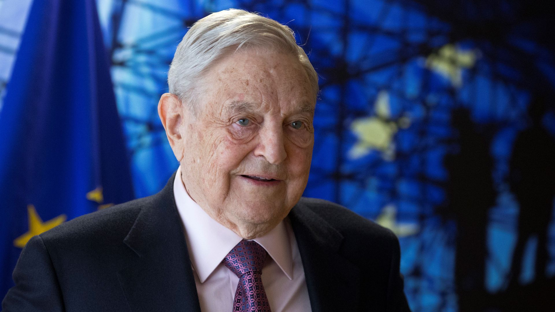 George Soros in front of the flag of the European Union