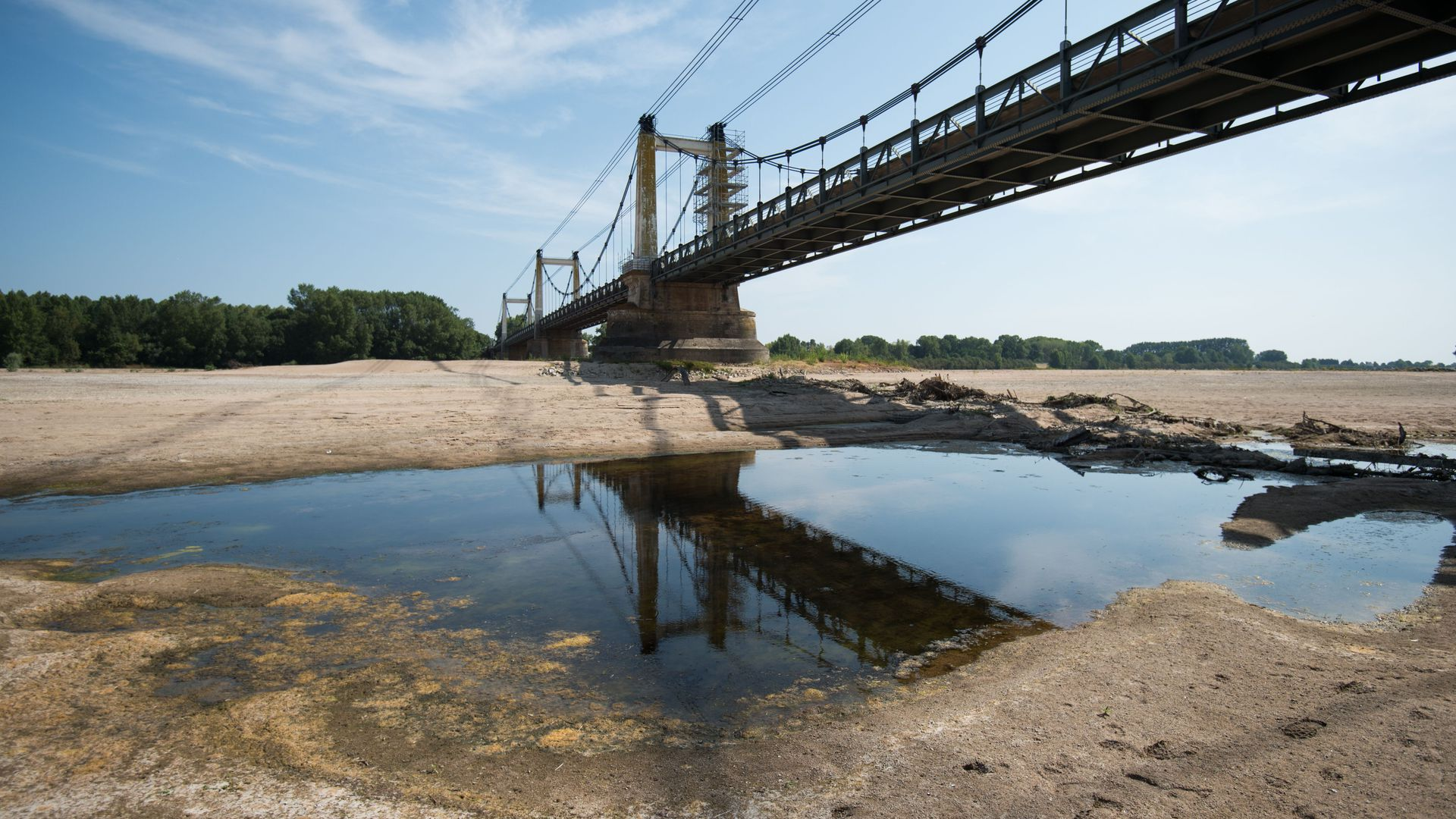 This image shows a mostly dry riverbed with a large bridge over it and trees in the distance