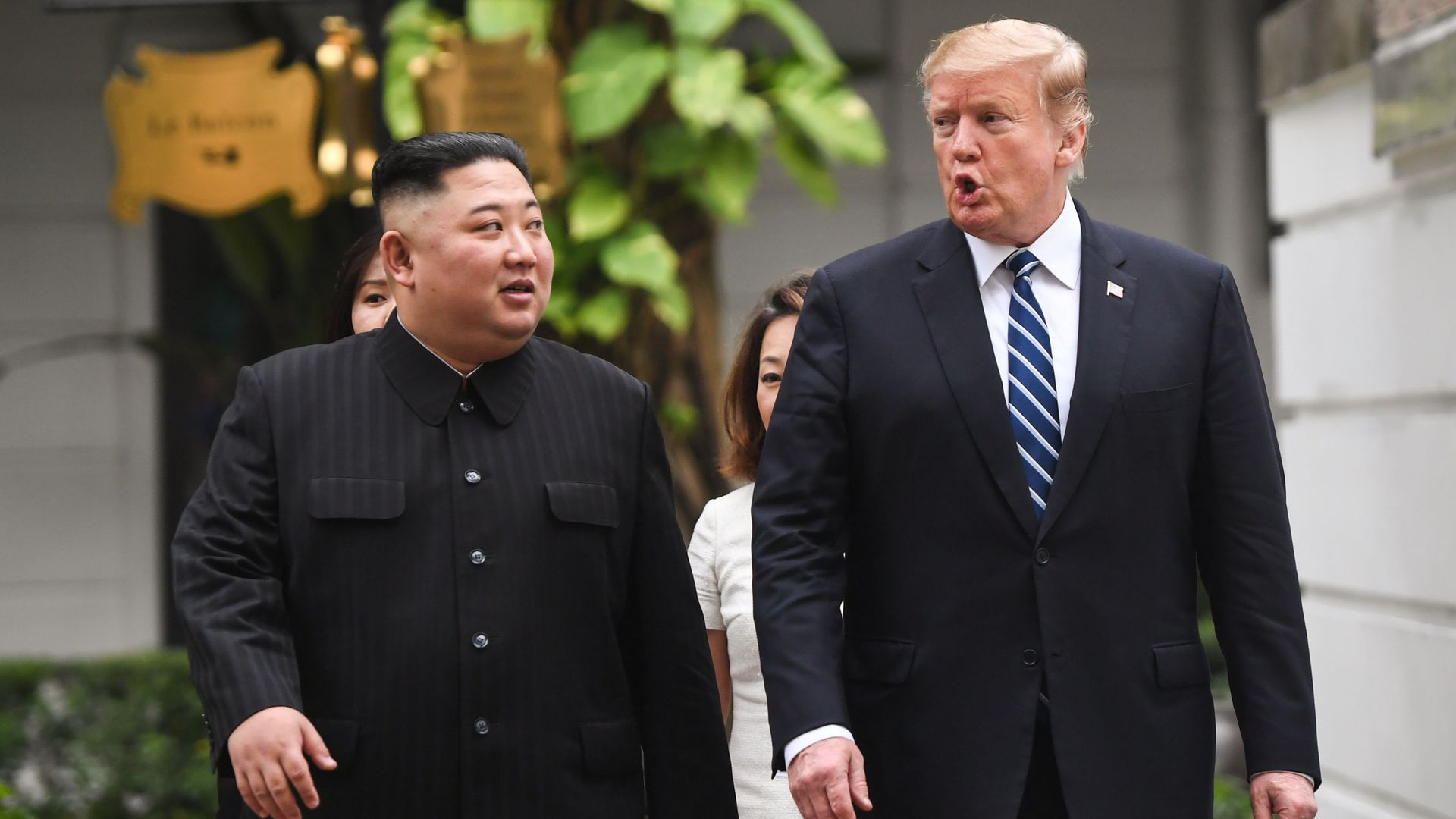 In this image, President Trump and Chairman Kim walk outside next to each other.
