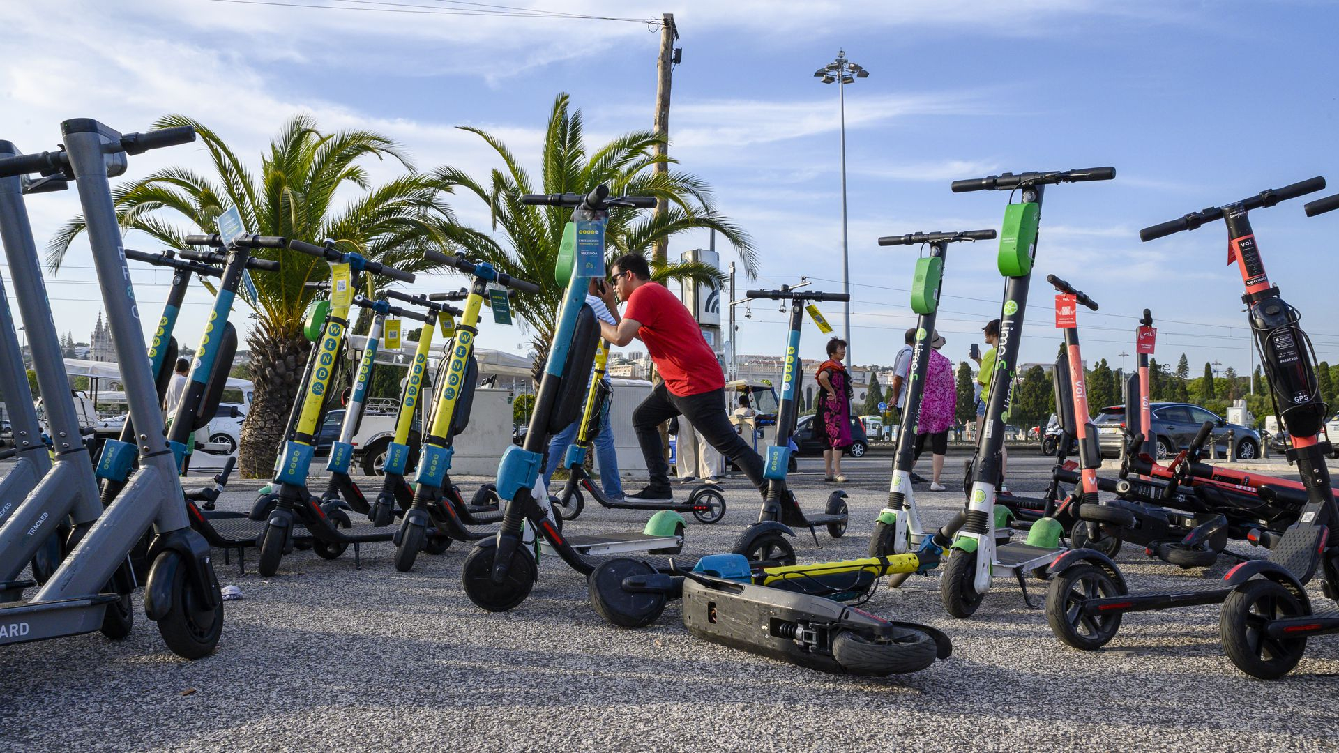 A man starts an e-scooter by a group of others left on an esplanade in Lisbon, Portugal
