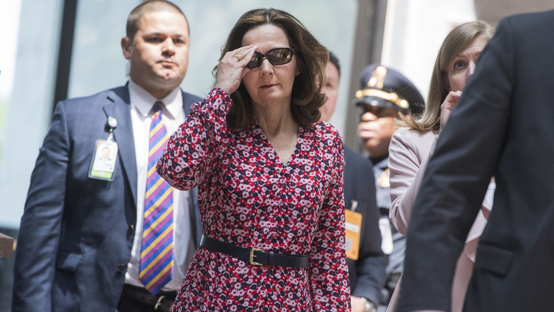 Gina Haspel holding her sunglasses, walking.