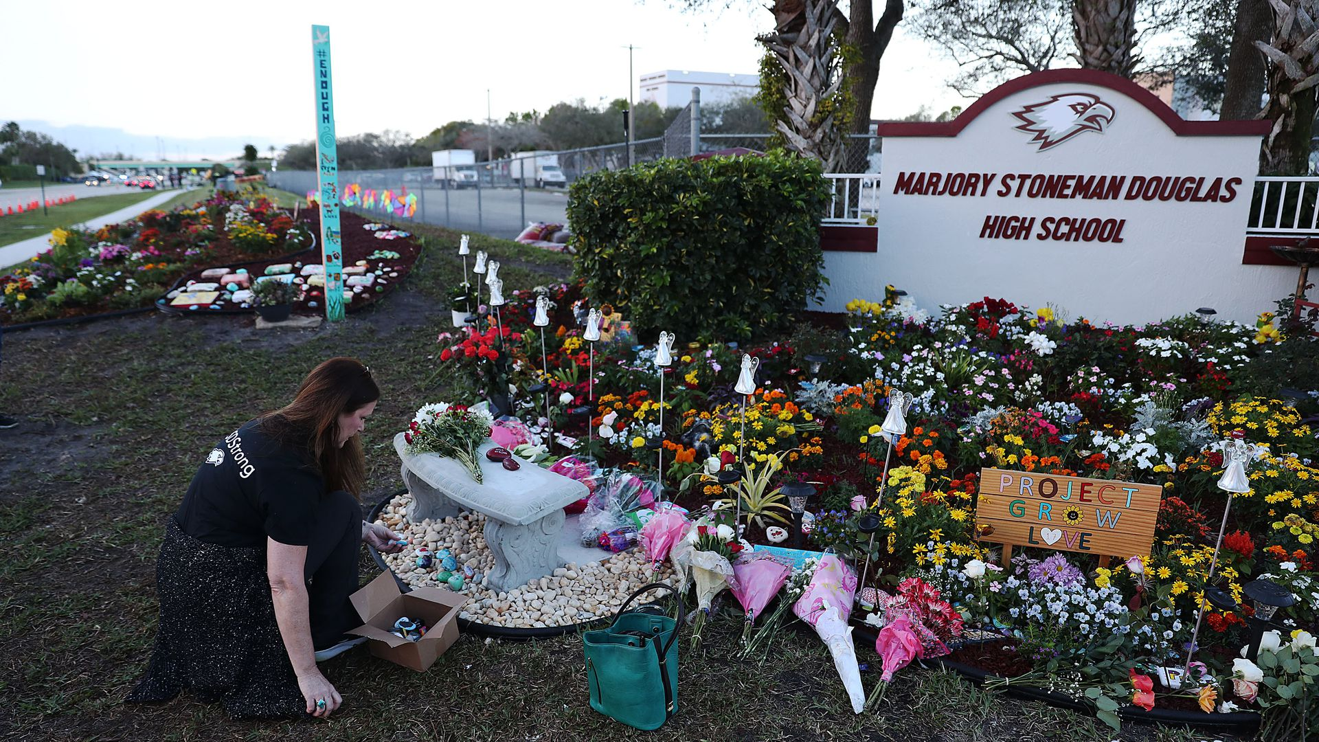 This image shows a large memorial of flowers and plaques underneath the Stoneman Douglas High School welcome sign.