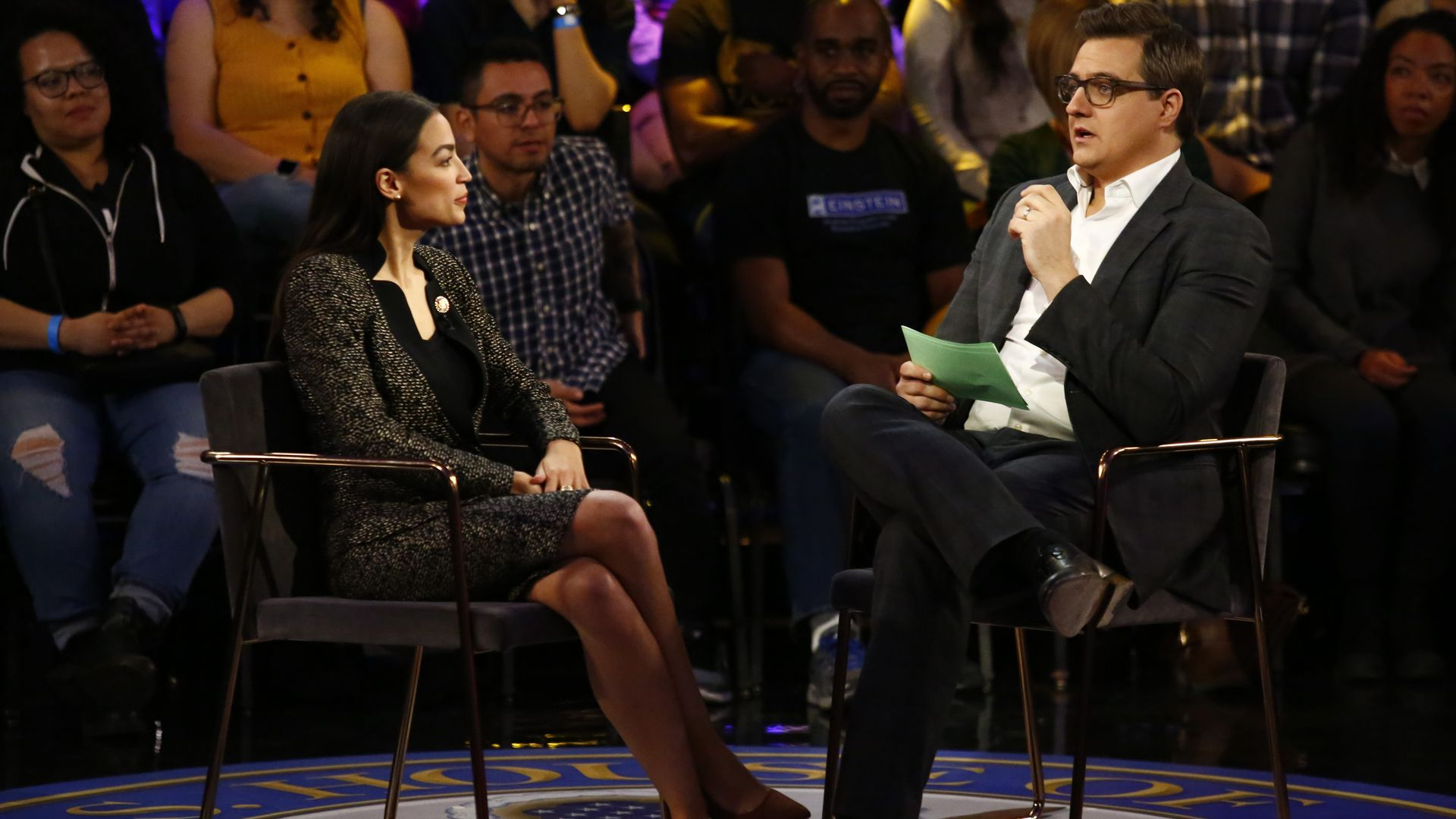 In this image, AOC and Chris Hayes sit across from each other on a raised circle platform at the townhall.
