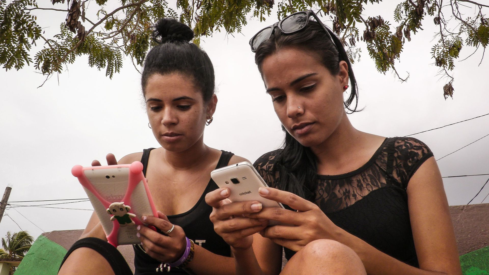 Young Cubans use WIFI on their cell phones
