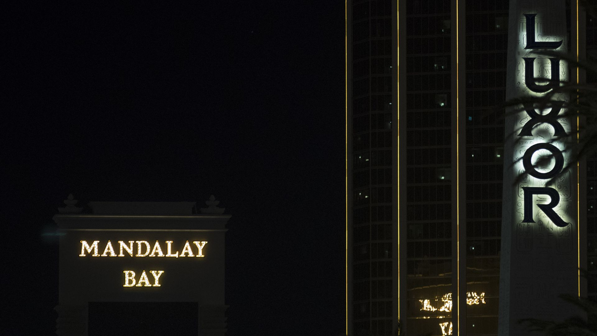 Mandalay Bay logo lit up in yellow with black background in nighttime.