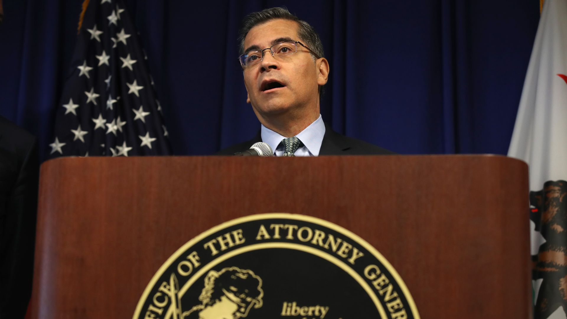 Photo of California Attorney General Xavier Becerra behind a podium next to an American flag